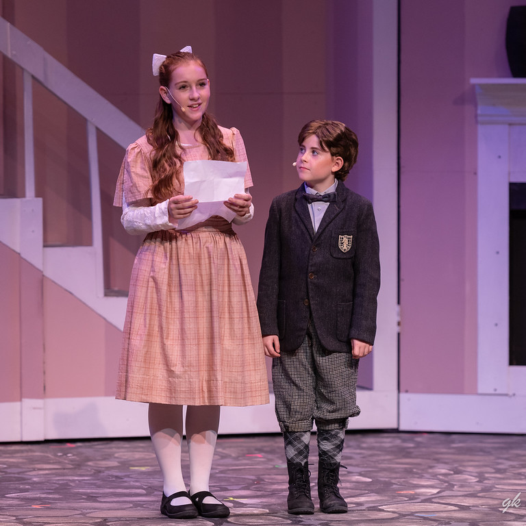 "Jane Banks (Ella Vitrano) reads a description of her perfect nanny along with her brother, Michael (Molly Flint), in a scene from Sunset Playhouse's ""Mary Poppins."""