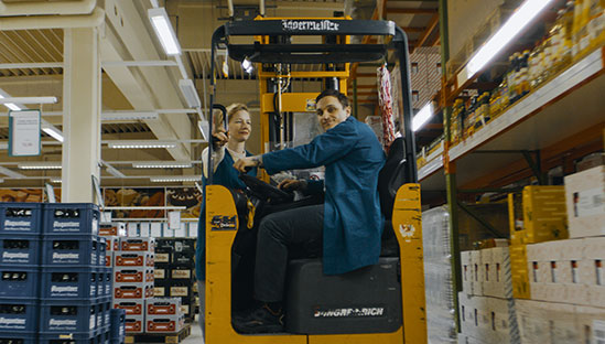 "Marion (Sandra Huller) and Christian (Franz Rogowski) take a ride on a forklift in a mega market in the workplace romance ""In the Aisles."""