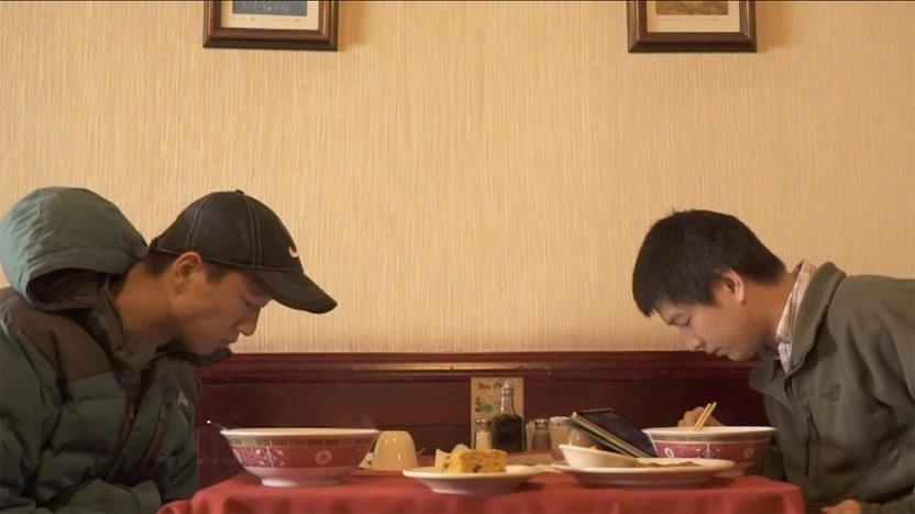 "The two Chen boys check their devices over a meal in ""Yen Ching."""