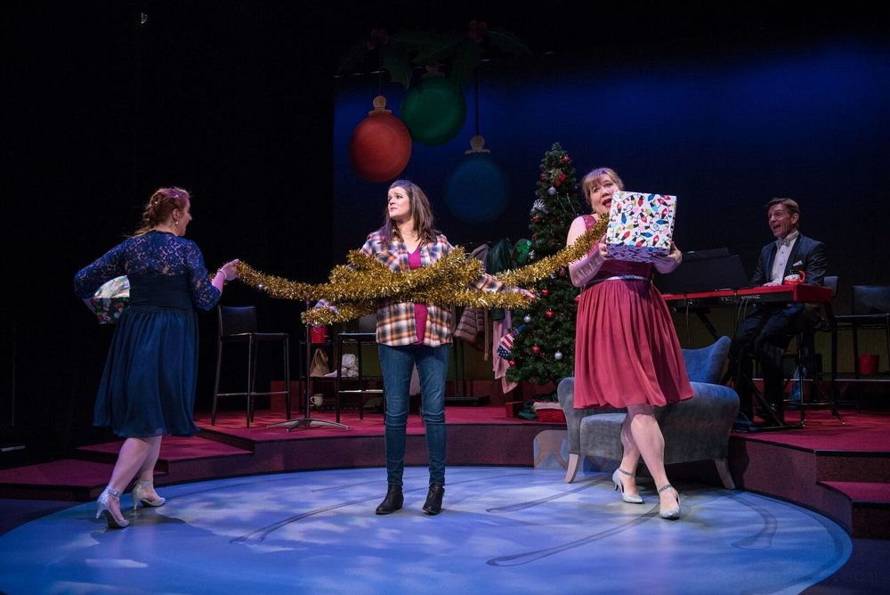 """The Doo Wop Duo (Marcee Doherty-Elst, left, and Kelly Doherty, right) and Jack Forbes Wilson on keyboards try to get Mary (Susie Duecker) in the holiday spirit with a sprightly tune during Next Act Theatre's """"The 12 Dates of Christmas.""""  Photos by Ross Zentner"""