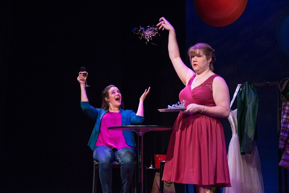 Mary (Susie Duecker) feigns her excitement as the New Year arrives with an unenthusiastic flourish from one of the Doo Wop Duo (Kelly Doherty).