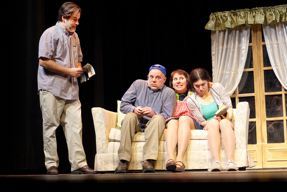 """Dad (Jim Mallmann) pages through a vacation guide to find a trip that appeals to his family — Don (Mike Owens), Mom (Karen McKinney) and Sis (Alexa Laur) in a scene from Falls Patio Players """"Leaving Iowa."""""""