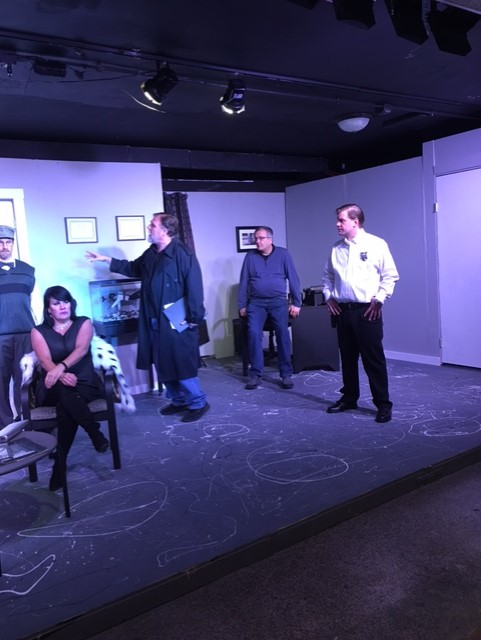 Officer Bartholomew (Mack Heath) interrogates suspects, from left, Melvin (Derek Jacobs), Carol (Rebecca Janny) and Barry (Al Van Lith). Officer Henry (Scott Tracy), right, guards the door.