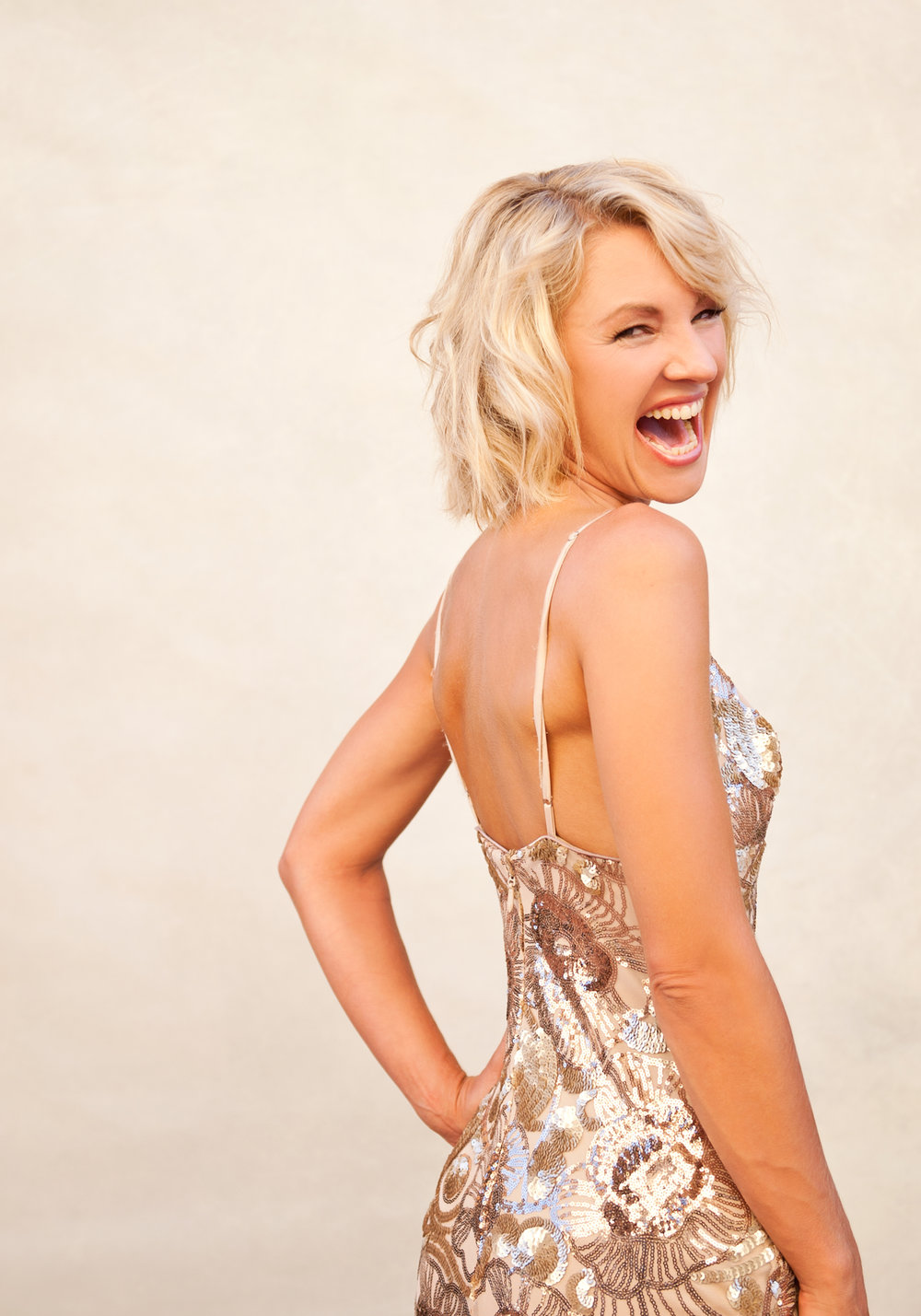 Blonde laughing girl with short hair in gold dress