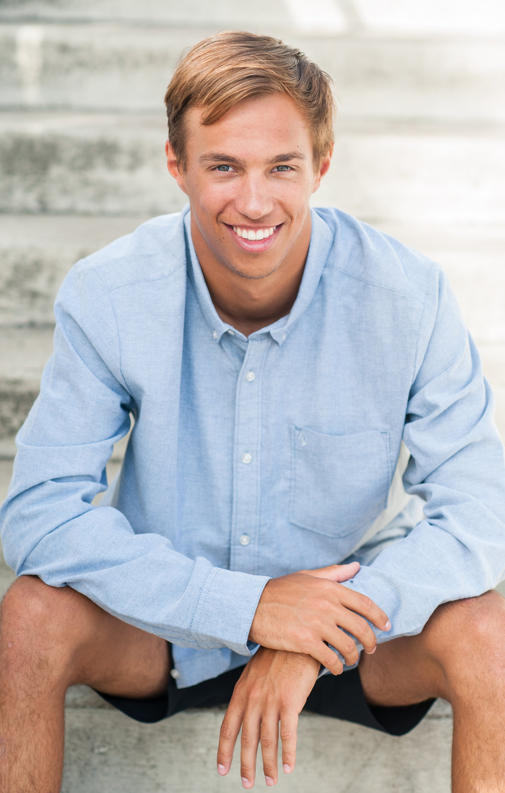 high school senior boy in blue dress shirt beach casual portrait