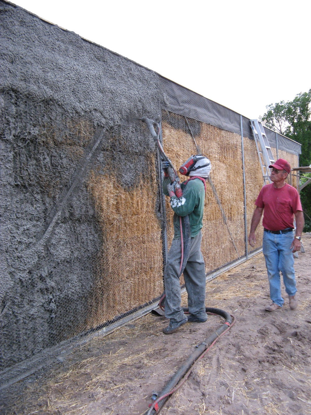 Tony starts spraying on the stucco