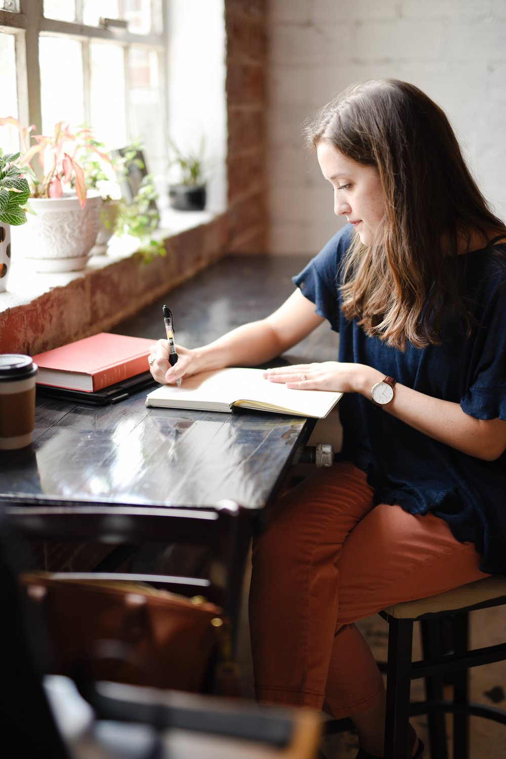 young woman journalling in cafe