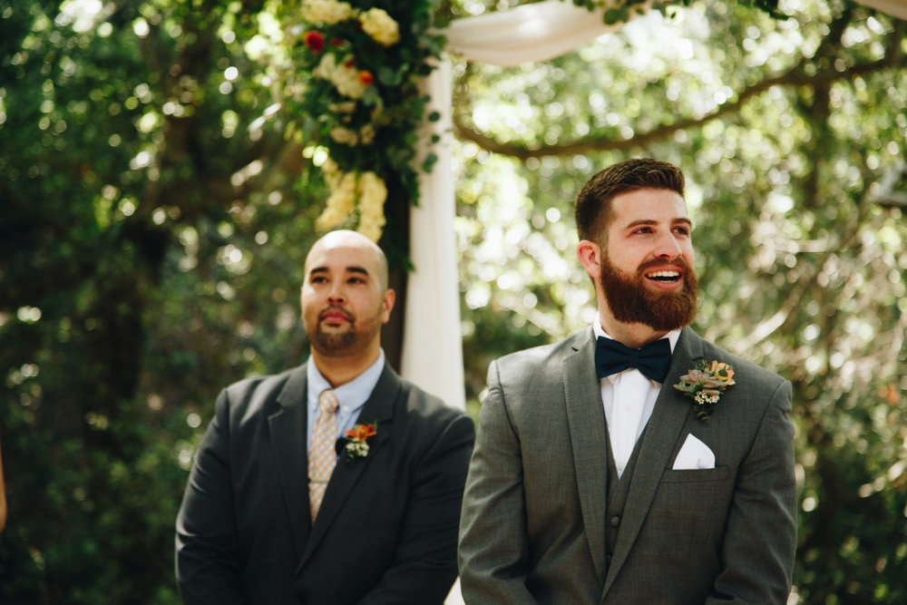 Through green foliage and tree branches, Jacob caught a glimpse of his bride. This is his raw first look completely stunned by his beautiful soulmate walking towards him. Our friend Tim Kothlow captured spot on.