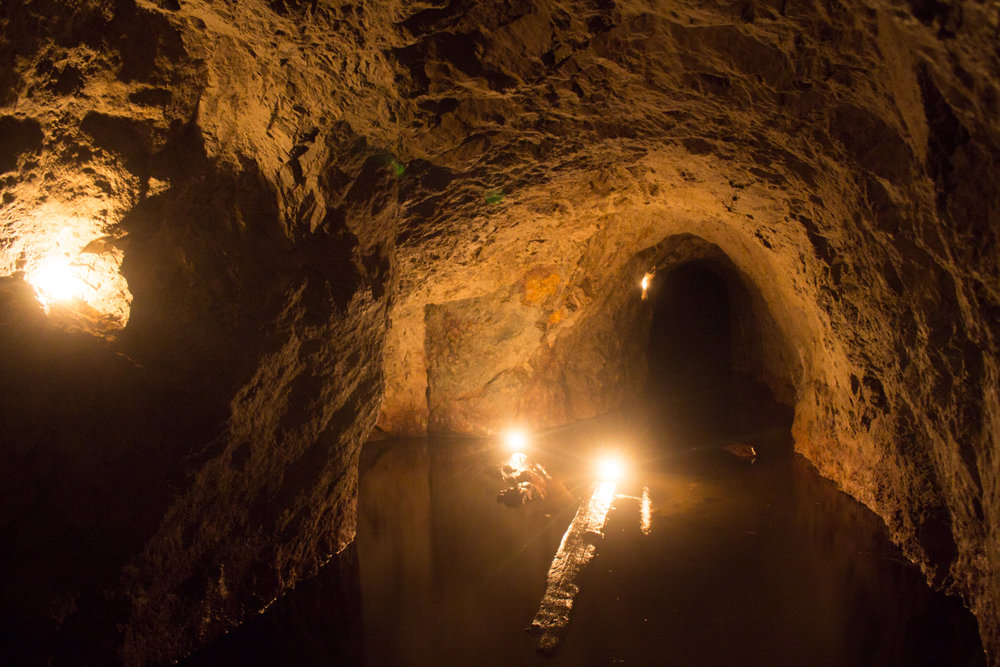 Inside the working of the mine, flooded passages and candle lit halls.