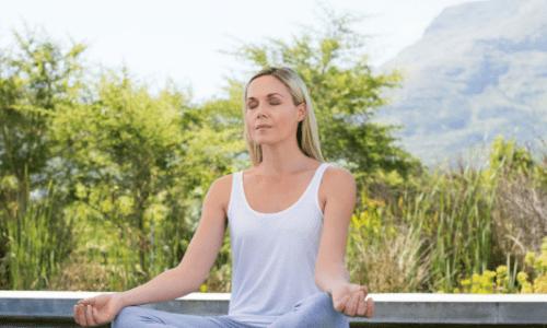 Blond woman meditating outside-min.png