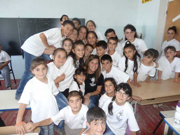 An AYF Youth Corps volunteer surrounded by children in Artsakh