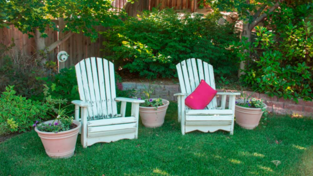 Two white outdoor chairs in the garden