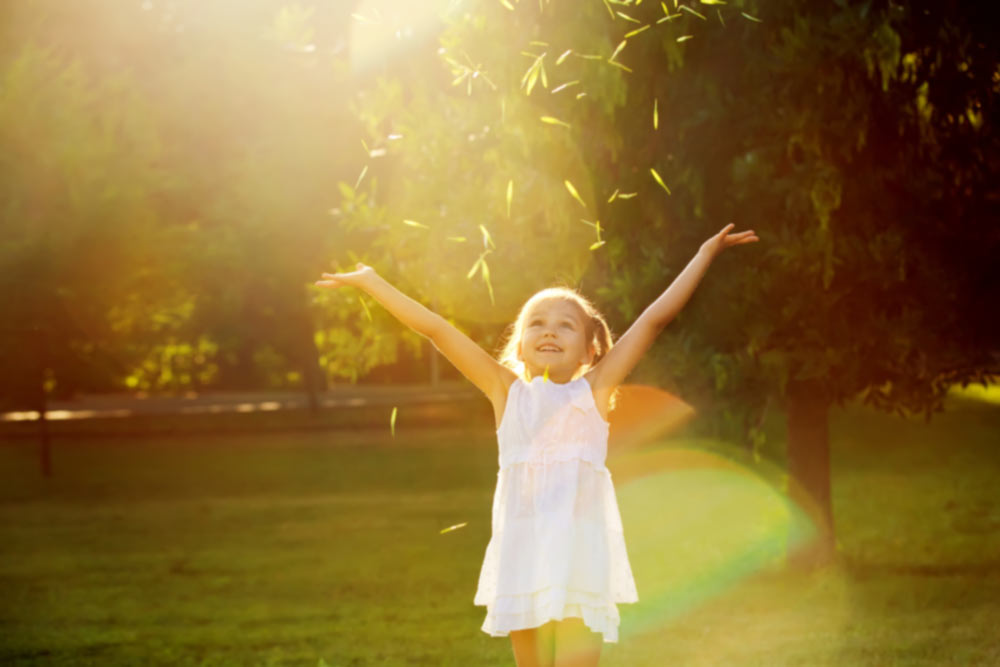 Small girl chucks up grass clippings in garden