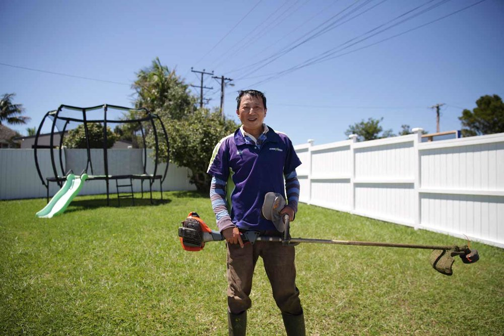 Auckland Crewcut operator stands in garden with line trimmer