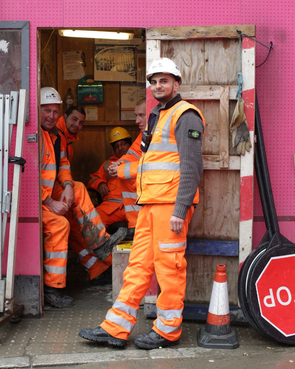 It was pouring down as I walked along Tottenham Court Road and saw Hussain, Dervis, George, Seol & Anil sheltering from the rain. They looked great in their orange flouris all sat together in a pink kiosk. If it wasn't raining they told me they'd be stopping traffic to let the lorries in and out of the construction site. They're were all so friendly and it soon turned into a mini photo shoot - they were really excited that I was going to send them copies of the photos because they're all friends on Facebook and wanted to share! They were really lovely guys and it turned into a mini photo shoot - theyeven took a photo of me with them all in the pink kiosk.