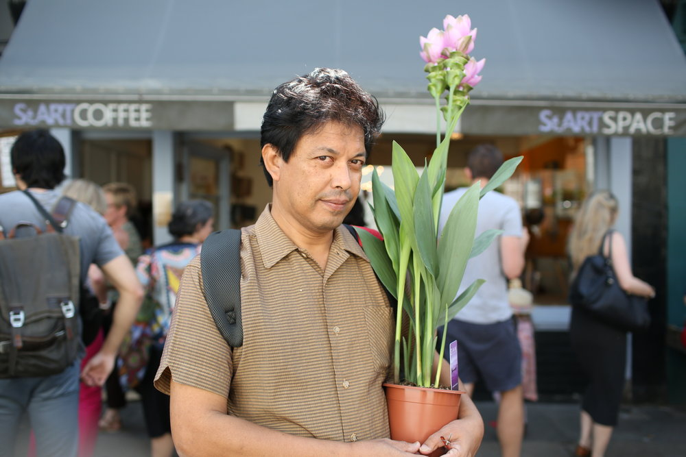 Kamal was so striking walking through the market with his Curcuma plant held aloft. He told me it's related to ginger and the roots are a tuber, very much like ginger. He told me (with a chuckle) that he'd bought it because he couldn't help but look more attractive carrying it. He had a mysterious and secretive plan to experiment with growing the plant. He didn't divulge much more so I was left intrigued.He usually lives in Malaysia and he's in London for just two months. In Malaysia he loves gardening so doing mysterious things with exotic looking plants is very usual for him!