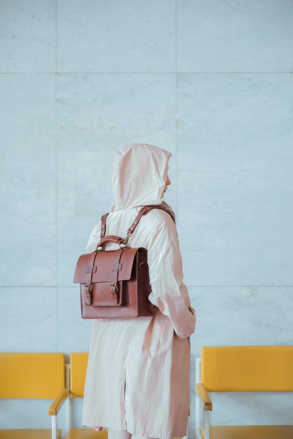 Model wearing saddle stitched luxury satchel with backpack straps