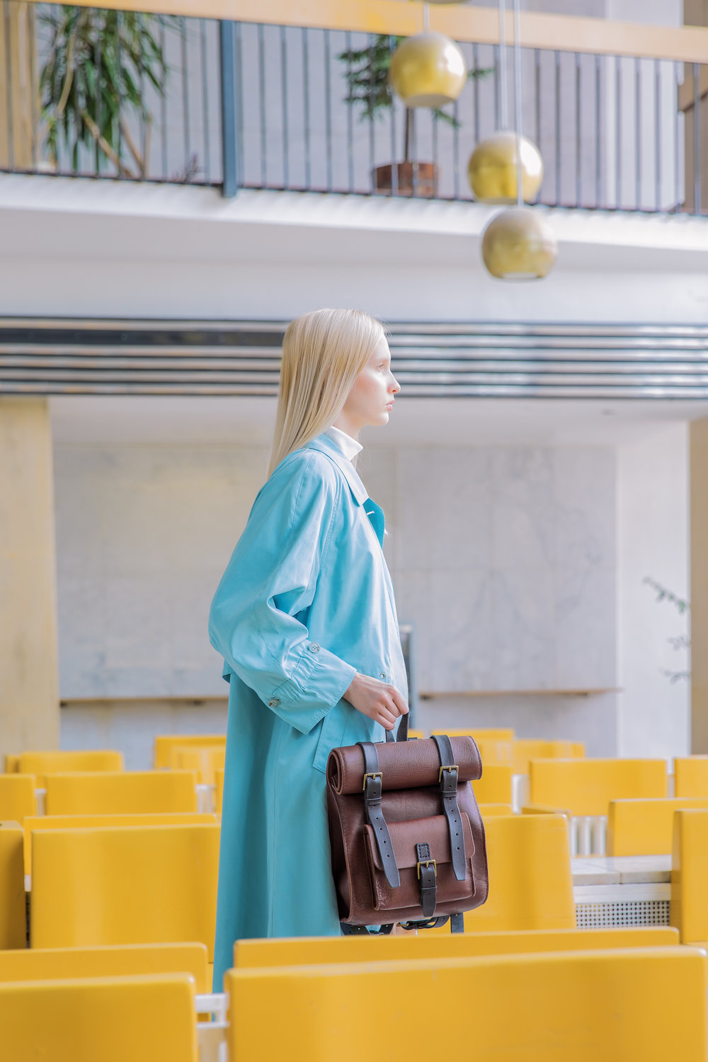 Brown leather backpack held by beautiful model
