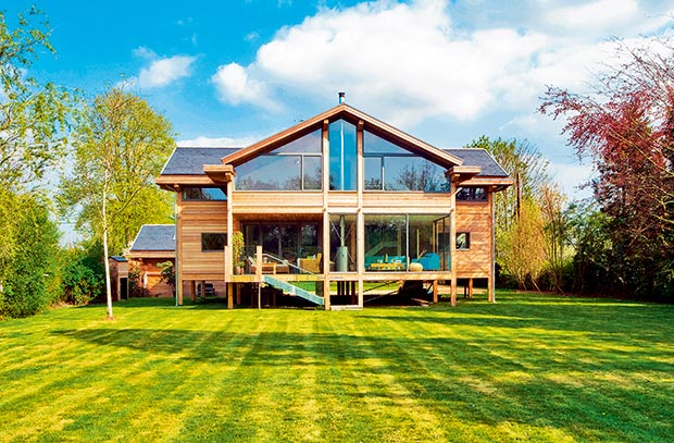 This house in Berkshire, near the River Thames, was built on a plot that was prone to flooding every year and so the house was built on timber posts, to match the set requirements.  Image Source:  Homebuilding & Renovating