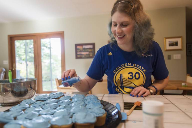 Emily Steffensmeier laughs with her mom, Renee, as they use blue icing to top cupcakes on Oct. 7 in their State College home. Steffensmeier has Dysautonomia and chronic fatigue syndrome and is organizing a walk to raise awareness and money for research. via Centre Daily Times