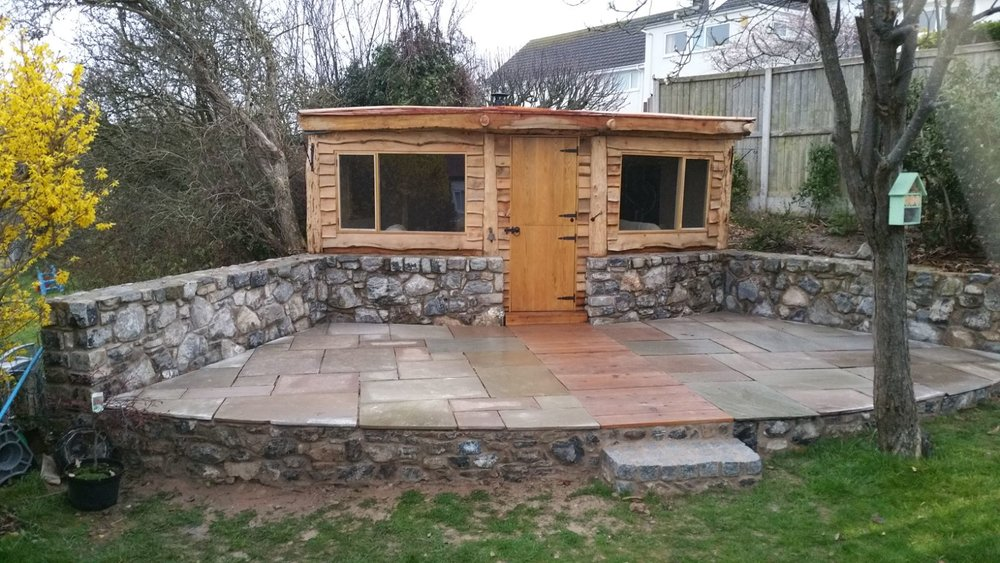 The Garden Chalet - The was a very unique project working with some exiting stonework. A wasted space in the corner of a garden we were able to merge together beautiful natural timber and welsh stone.The dimensions were 4 metres square. The posts and cladding were larch and the stable door & windows were handmade using oak. On top is a larch shingled roof and theres even a log burner inside to make it cosy.