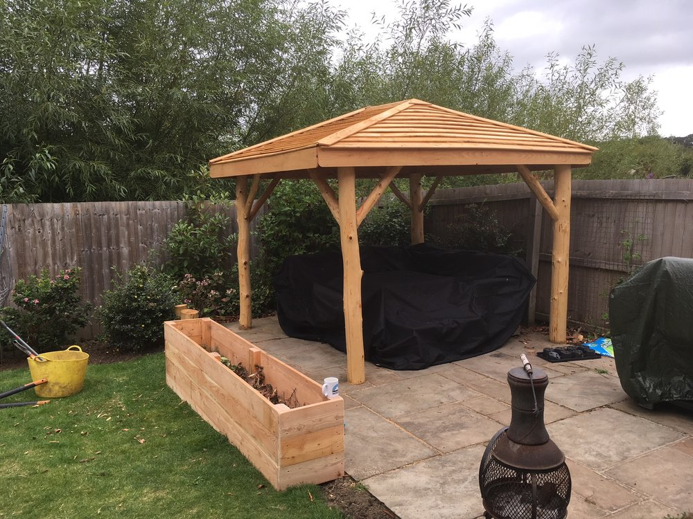 The Gazebo - A simple but perfectly formed gazebo that brings a little rustic charm to a blank canvas.Whether its to shelter from the sun or rain this gazebo is perfect for creating a wonderful natural social space.Built using welsh larch from our woodlands it offers a beautiful contrast with straight lines in the roof and natural curves in the poles.These gazebos would also be ideal for covering outdoor hot tubs for those more exclusive garden spaces!