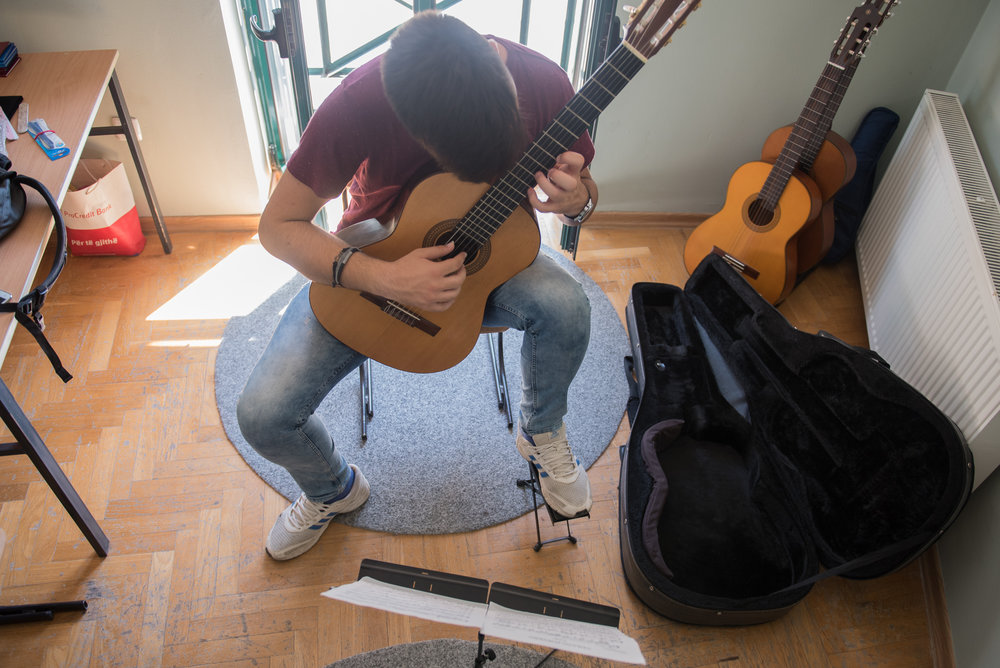 Lorik Pylla practices his guitar in the guitar classroom of the Prenk Jakova high school, Gjakova, Kosovo, July, 10, 2017.  Pylla averages between three and four hours of practice time a day.