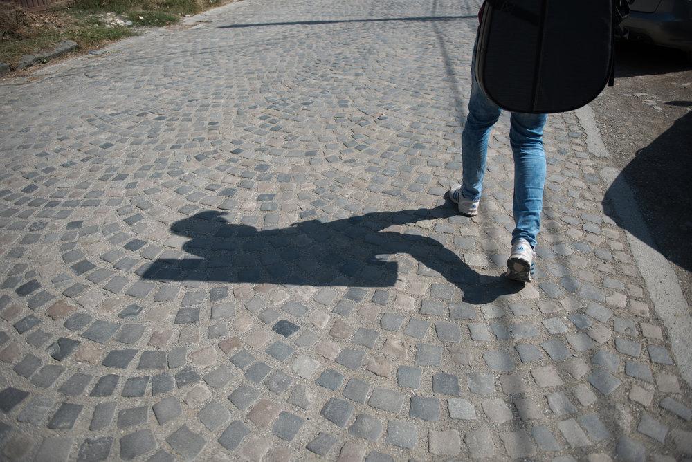 Eighteen-year-old Lorik Pylla walks down the street carrying his guitar on his back in Gjakova, Kosovo, July 10, 2017.