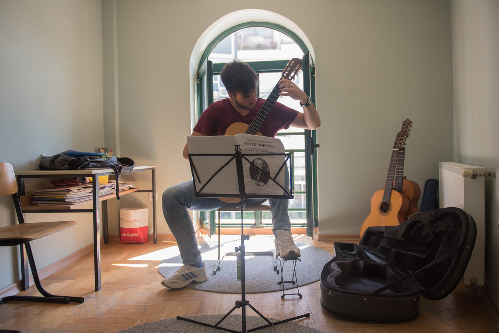 Lorik Pylla practices his guitar in the guitar classroom of the Prenk Jakova high school in Gjakova, Kosovo, July 10, 2017.