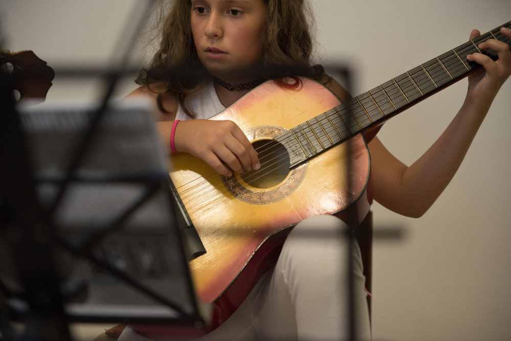 Rita Nushi plays guitar during her practice session with Lorik Pylla in Gjakova, Kosovo, July 10, 2017.