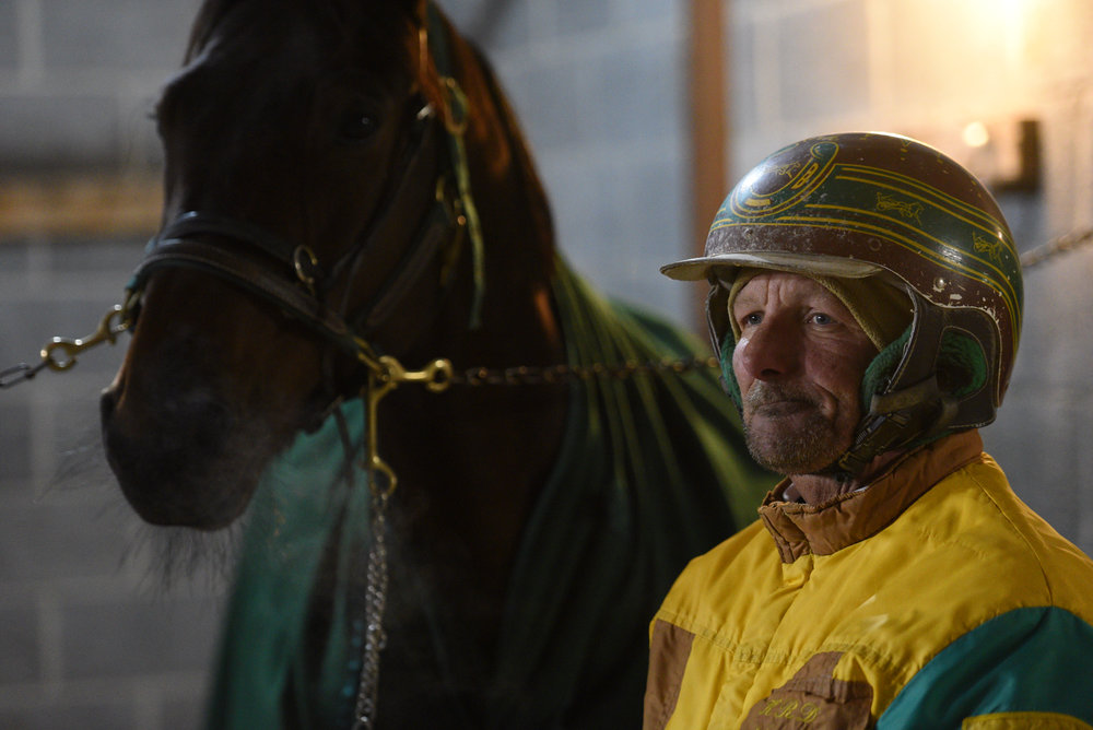 Kirk Desmond stands with a horse prior to the start of his next Harness race at Batavia Downs in Batavia, N.Y. on Nov. 10, 2017.