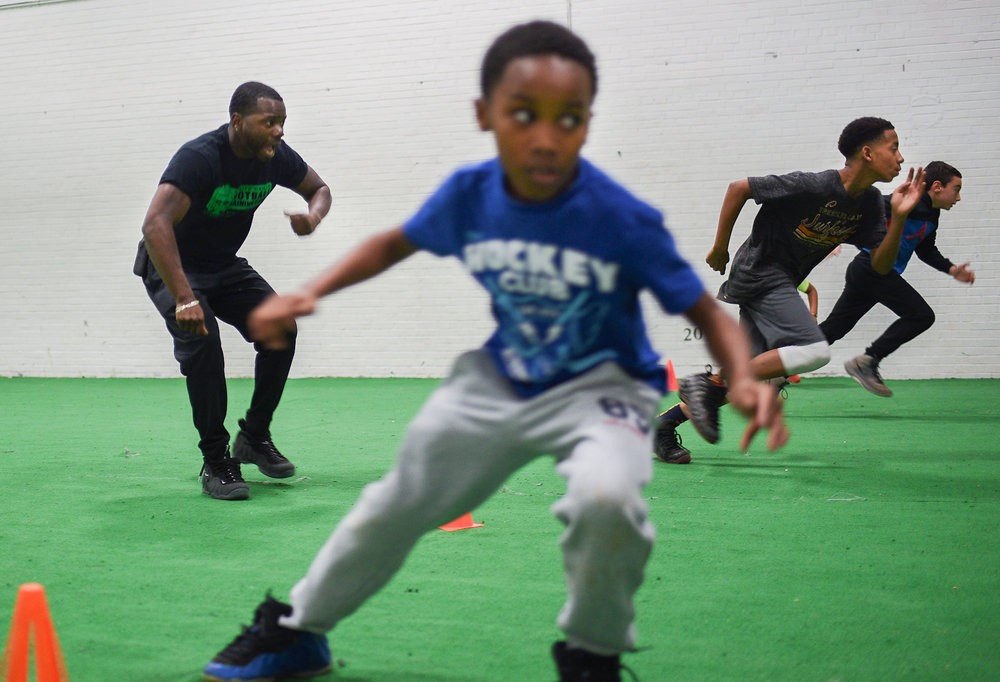 Greg Hopkins directs athletes while they participate in a series of running drills during the biweekly football mentor program at Lincoln Sports Park in Rochester, N.Y. on Dec. 7, 2017.