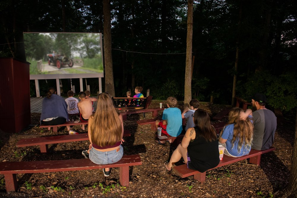 Campers on Benches Watch an Outdoor Night Movie at Cherry Hill Park