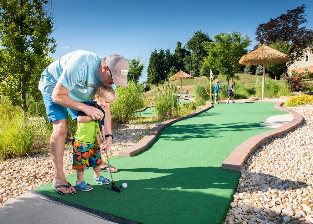 Father Helps Son Hit Ball on Mini Golf Course at Cherry Hill Park