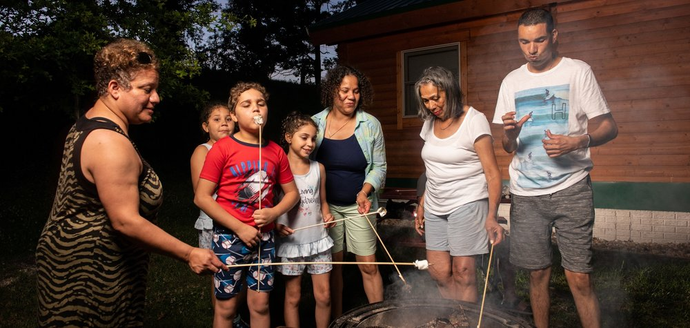 Family Roasting Marshmallows Outside a Premium Log Cabin at Cherry Hill Park