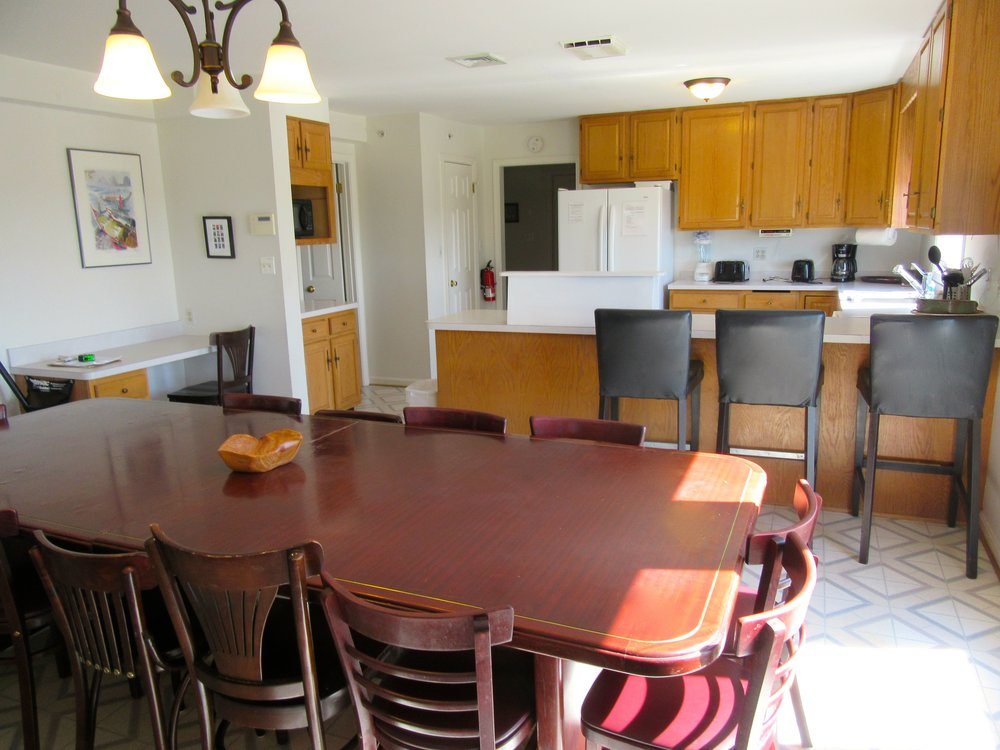 Cottage Kitchen and Dining Room with Large Wooden Table and Counter Stools