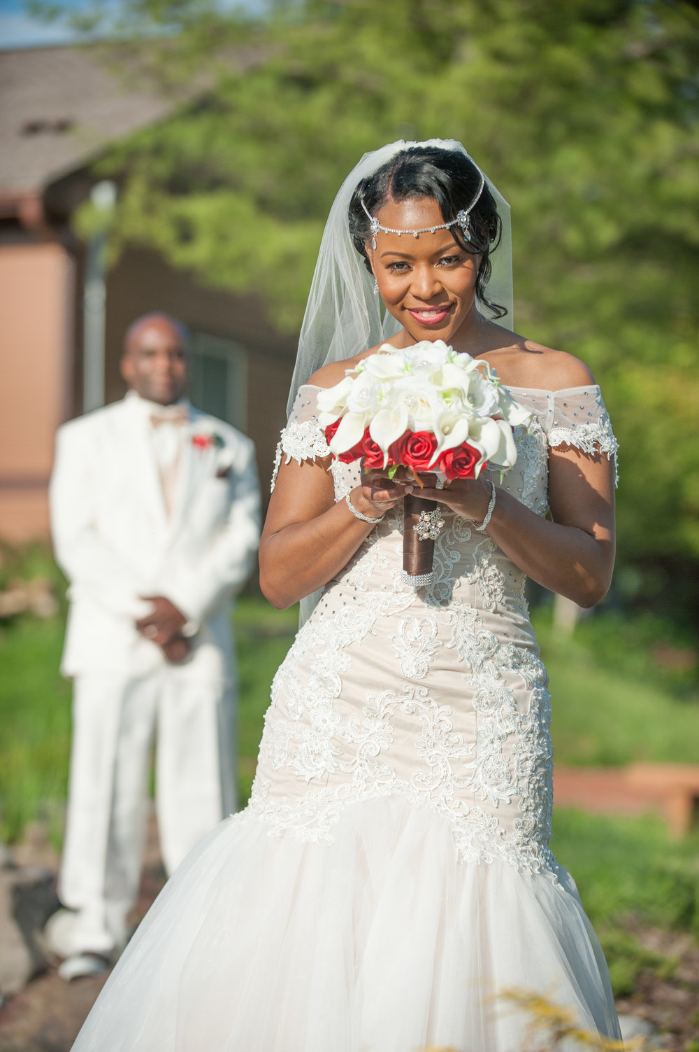 Bride with Bouquet Smiles with Groom in Background