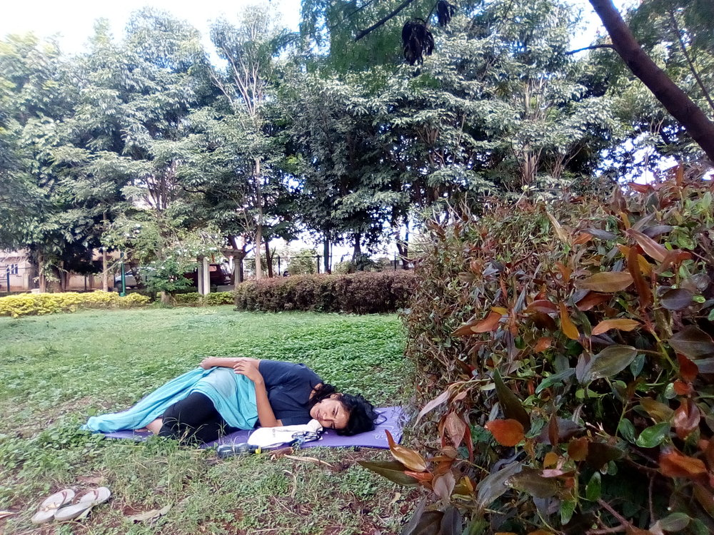 My name is Pahi Gangwar and I was participating in the MTS event from Bangalore.  I did this by myself in a small BBMP-maintained park near my house in Hebbal.    I chose not to go to Cubbon Park because I felt that if I were to do this, I'd do it how it would be done in a utopic, ideal world. I was in the park from 1:15 till 3:30 PM. My heart was pounding as I entered, picked a spot and eased myself into lying down. Since I was absolutely alone, I took a book and two bananas as my decoy; put a leaf between the pages and held the book real close to my body and shut my eyes. Every rustle felt like someone had walked up to me, the wind felt like it was blowing away my sheet and shirt and my skin was showing, all the sounds around me were amplified by double. But my body just wouldn't let me fall into sleep. So I did the best I could and shut my eyes for really long so that everyone who saw me, thought I was asleep. When I 'woke up', a few men and women were looking at me off and on but it didn't look like they cared more. Two boys were sitting close-by on the grass but I didn't seem to be bothering them either so I clicked a few pictures and came home.  In retrospect, I'd like to do this again but with one(any) other person; just to experience it differently.  Thank you for taking the initiative! I was particularly moved by the line 'Sleep is surrender in trust'.