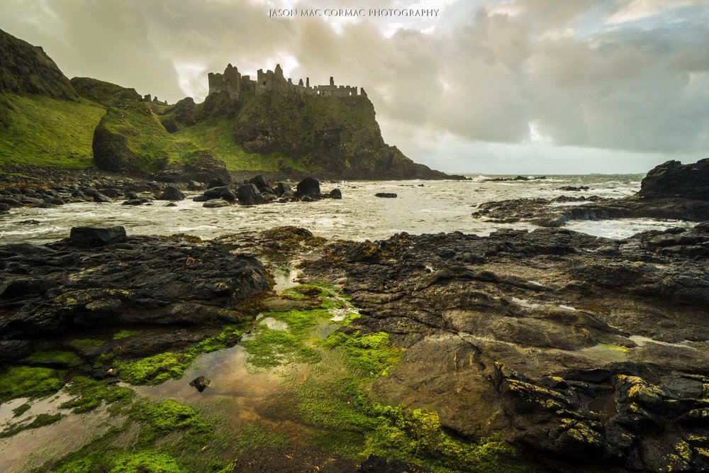The rock pools and algae leading the eye into the scene to Dunluce Castle