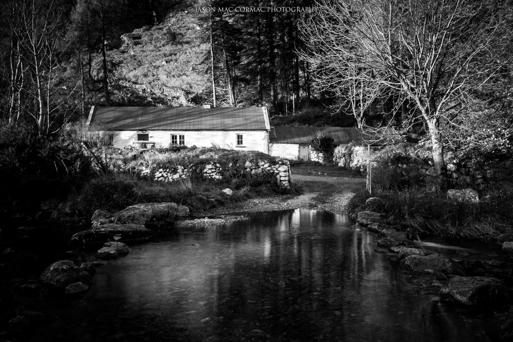 A black and white image of the cottage and the river.