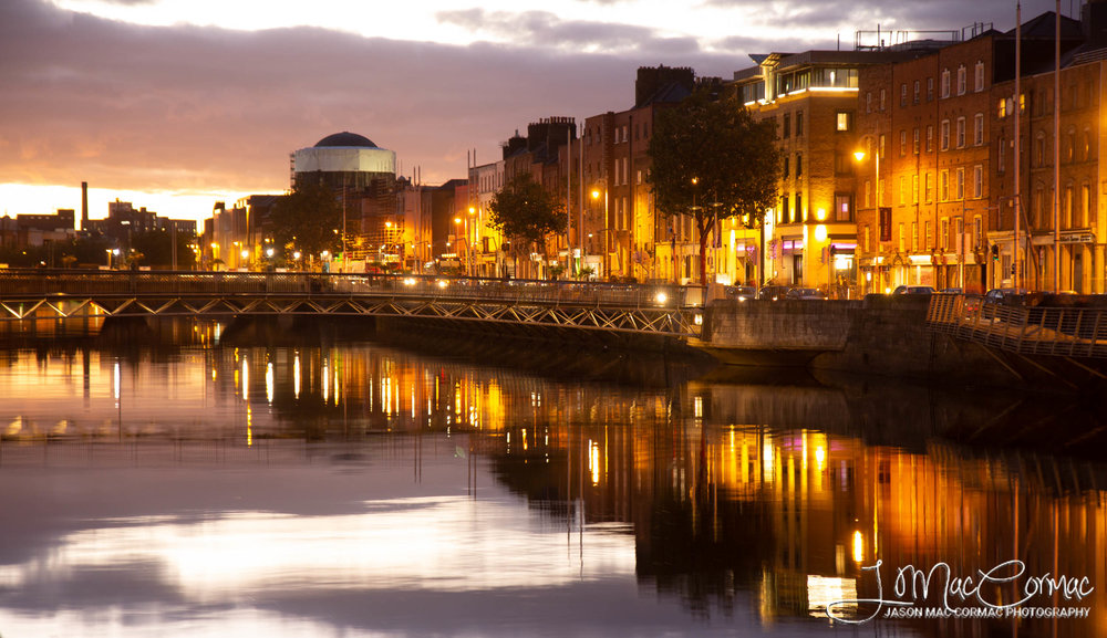 Dublin bathed in golden light reflecting in the River Liffey.