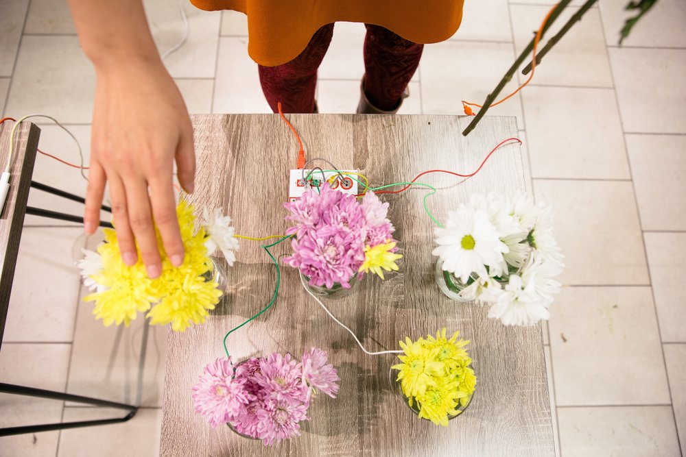 Touch a canary yellow flower and a cat meows.  Touch a white flower and a bell jingles.  Code Park shares the magic of circuitry with flowers and sounds at Pop Shop, Houston, December 2017.  Photography courtesy of Jessi Bowman.