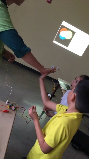 """Students complete a circuit by giving Wanjun a high-five and the circles move. """"How does it work?"""" they ask. Leonel Castillo BakerRipley Community Center, Fall 2017. Photography courtesy of Amanda Shih."""