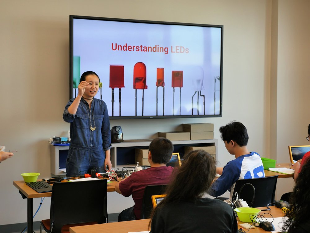 Code Park's Invent to Learn in action! Students learn from Wanjun about LEDs to built a circuit and program how they light up in Python at the East Aldine BakerRipley Fab Lab, July 25th, 2018.  Photograph courtesy of BakerRipley.