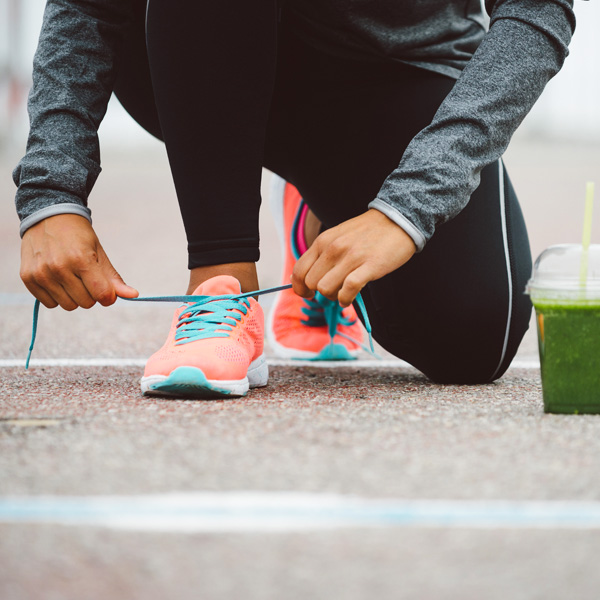 Jogging woman putting down her smoothie to tie her shoelace