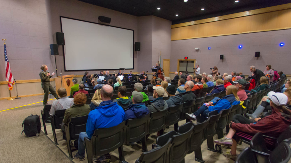 Chief of Interpretation Nancy Holman welcomes audience to composers' concert at the Denali Visitors Center.