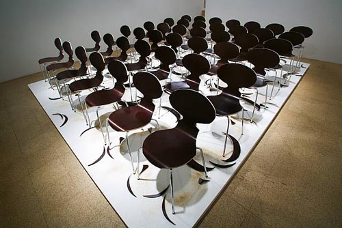 SUPERFLEX, Copy Right, 2006, Eighty brown chairs, sawdust, wood cut-outs & platform