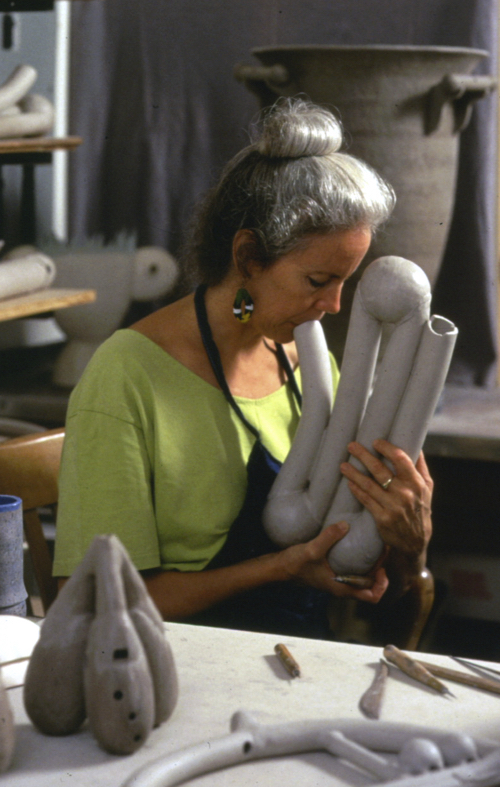 Image: Ms. Rawcliffe in her studio; in the foreground, there is a triple ocarina and a round ceremonial multiperson instrument with whistles & flutes. In the background are the Whistling Pot for 3, and a two person chamber duct piece, After the Ball. Both can be seen finished on the Gallery page.