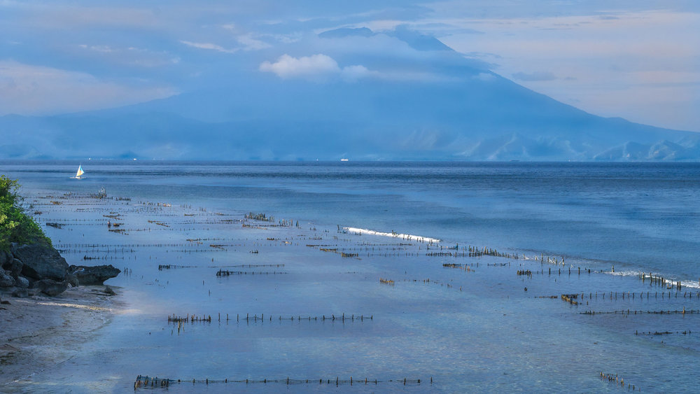 The view of Mount Agung from the island of the shores of Nusa Penida island.