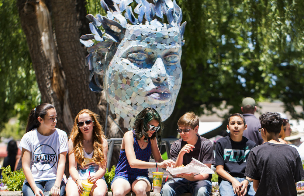 Teens hanging out with sculpture at Blues 2016.jpg